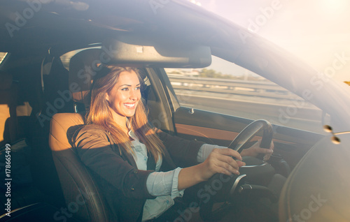 Leinwand Poster Beautiful businesswoman driving car at sunset