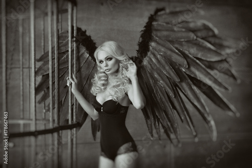 Fotografie, Obraz  blond woman with black wings in a cage. Angel, mysticism
