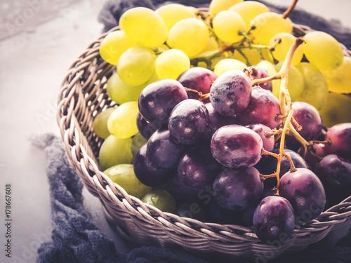 Plakat Białe i ciemne winogrona w koszu na szaro. Streszczenie minimalne owoce martwa