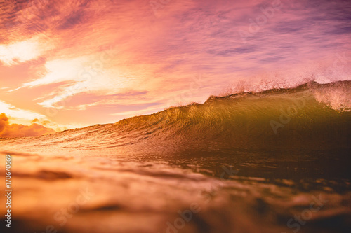 Fotobehang Rood paars Wave at sunset or sunrise in ocean. Wave and with warm sunset or sunrise colors