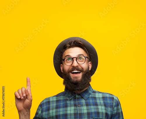 Photo  Content man pointing up on orange