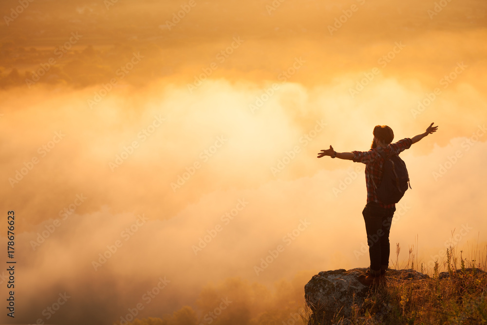 Fototapety, obrazy: Man on stone above clouds