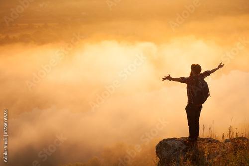 Fotografia  Man on stone above clouds