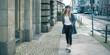 Panoramic view of smiling girl walking through urban city street.