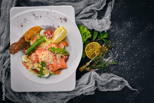 Obraz na dibondzie (fotoboard) Sałatka z łososiem solonym, serem i liśćmi sałatkowymi. Na drewnianej powierzchni. Widok z góry. Wolne miejsce na Twój tekst.