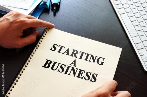 Fényképezés  Book Starting a business on a desk.