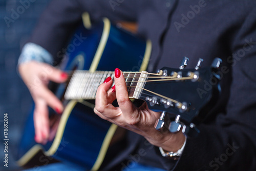 Fotografering  Close-up female hand playing on acoustic guitar.