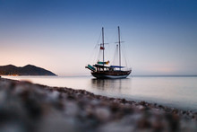 Tourist Sailing Ship On The Quay In The Bay Near The Coast With The Beach At Night