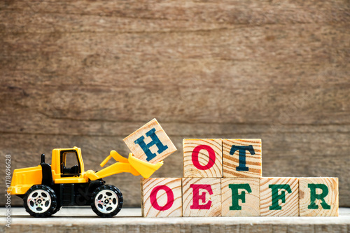 Keuken foto achterwand Toy plastic bulldozer hold letter block H to complete wording hot offer on wood background