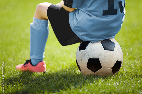 Deurstickers Bol Child Sitting on Soccer Ball. Young Boy with Soccer Ball on the Pitch. Soccer Grass in the Background. Younth Sport Football Background