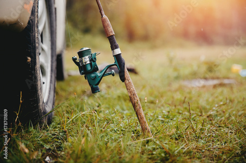 Zdjęcie XXL Wędkarstwo. Zbliżenie wędki z prętem do łowienia ryb, stoi w pobliżu koła samochodu. Podróże koncepcyjne, rekreacja dla mężczyzn