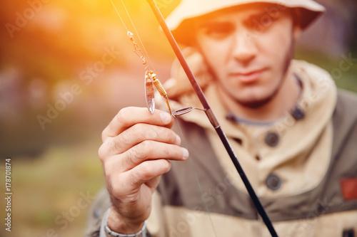 Zdjęcie XXL Wędkarstwo. Zbliżenie: rybak trzyma hak i przynęty, przynęta do łowienia ryb