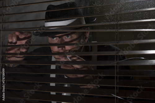 Mature man dressed in 1940s fashion smoking a cigarette looking out of a window, Canvas Print