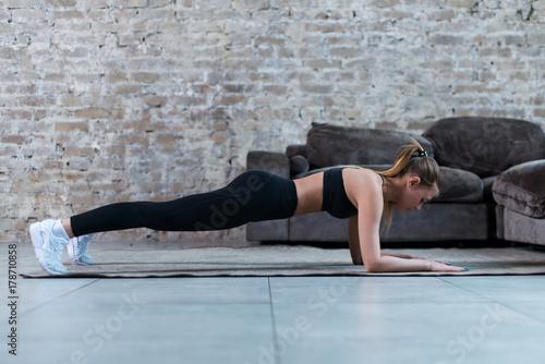 Fotografie, Obraz  Slim young brunette wearing black gym clothing doing abdominal bridge or front plank exercise in loft apartment