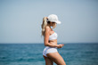 Young beautiful woman in sport suit is using her tablet on the beach