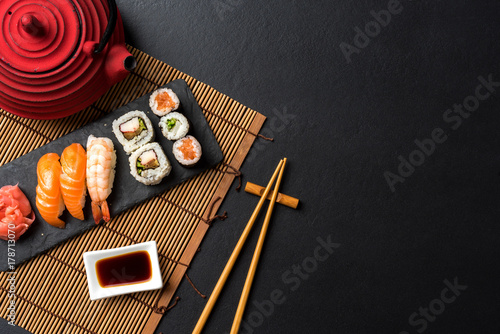 Poster Sushi bar Set of sushi with wasabi, soy sauce and teapot on black stone background. Top view