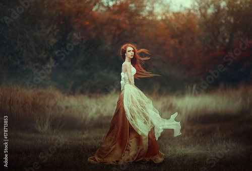 Beautiful young woman with very long red hair in a golden medieval dress walking through the autumn forest Wallpaper Mural