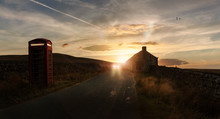 Car Travelling On Rural Road With Telephone Box And House At Sunset