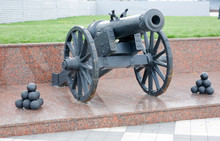 An Old Cannon On A Granite Pedestal