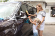 Woman with little daughter washing car outdoors