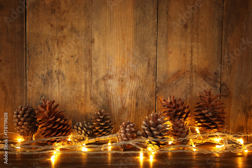 Foto  Holiday image with Christmas golden garland lights and pine cones over wooden ba