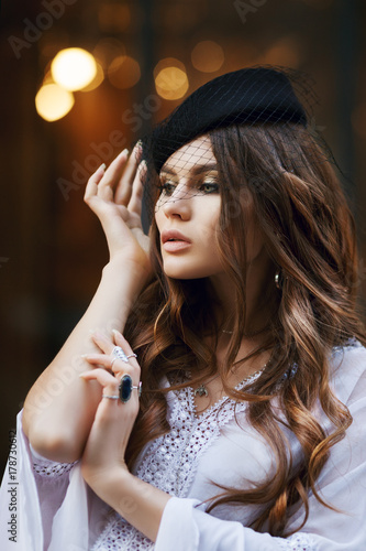 Poster Gypsy Outdoor close up portrait of young fashionable woman wearing hat with veil posing in street. Model has beautiful long hair. Lady wearing stylish clothes. lights on background. Female fashion concept