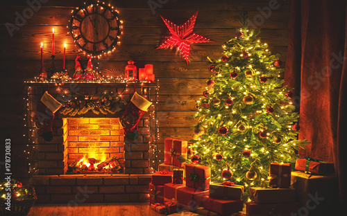 Fotomural interior christmas. magic glowing tree, fireplace gifts in  dark