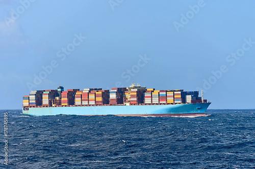 Plakat Duży niebieski kontenerowiec z kontenerami na pokładzie z boku
