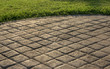 canvas print picture - Stamped concrete pavement cobblestones pattern, decorative appearance colors and textures of paving cobblestones tile on cement flooring in a park with green lawn