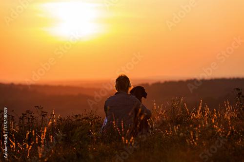 Poster Marron chocolat Frau umarmt ihren Hund im romantischen Sonnenuntergang