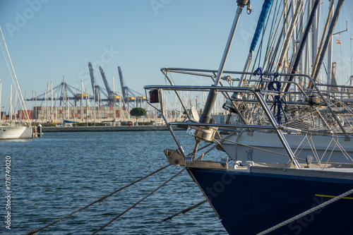 Fotografía prow of a sailboat, blurred background a commercial port with cargo containers