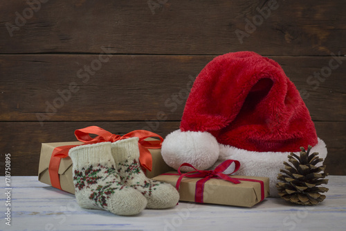 Santa Claus hat, gift boxes, knitted socks, cone. Focus on a gift box with scarlet ribbon #178750895
