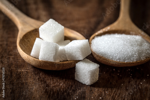 sugar cubes and cane in wooden spoon on the table ,retro color tone