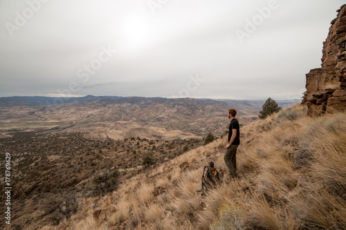 Fotografie, Obraz  Tall young man on mountainside while Backpacking near the Painted Hills