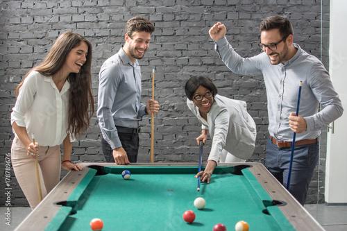 Plakat Rozochocona biznes drużyna bawić się bilardowego po pracy.