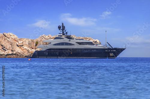 Plakat Duży luksusowy jacht zadokowany na morzu, ale gotowy do podróży do tropikalnej pięknej wody