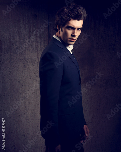 72ac3980 Sexy handsome male model posing in blue fashion suit and white style shirt  looking down on dark shadow background. Toned portrait