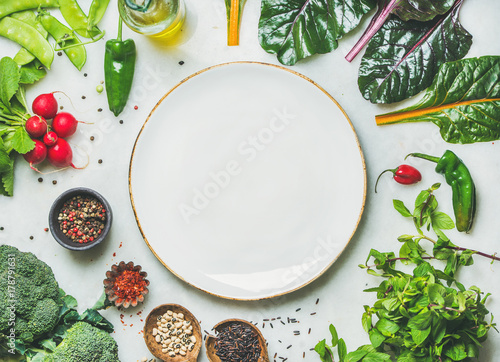 Photo  Fresh raw greens, unprocessed vegetables and grains over light grey marble kitchen countertop, wtite plate in center, top view, copy space