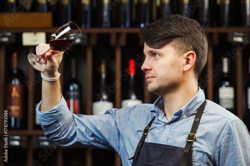Fotomural Bokal of red wine on background, male sommelier appreciating drink