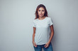 Leinwanddruck Bild Sexy woman in a white T-shirt on a gray background. Mock-up.
