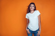canvas print picture - Sexy woman in a white T-shirt on the orange background. Mock-up.