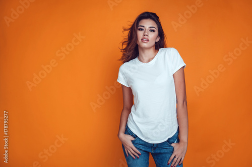 canvas print motiv - kanashkin : Sexy woman in a white T-shirt on the orange background. Mock-up.