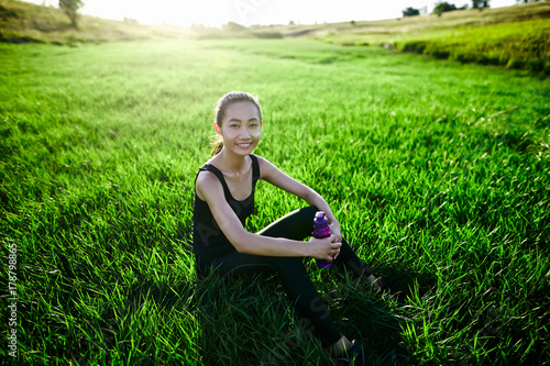 Sports girl relax on grass with bottle looking into camera