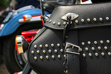 Closeup Of Black Leather Motorcycle Saddlebags With Rhinestone Studs, Cruiser Motorcycles In Back