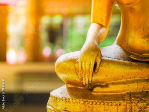 Plakat ręka złoty posąg Buddy, ręka na kolana i siedzi ze skrzyżowanymi nogami.