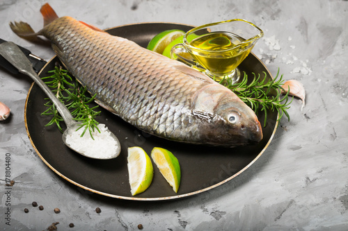 Plakat Surowa ryba z świeżymi zielonymi rozmarynowymi liśćmi wapno oliwa z oliwek na kulinarnej niecce, zdrowy łasowania diety jedzenia pojęcie.