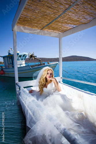 Fotografie, Obraz  Beautiful blond woman with long legs in a white ball gown wedding dress it is ly