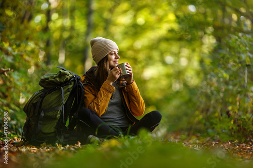 Foto  Beautiful brunette tourist girl wears cap and backpacked have break with cup of