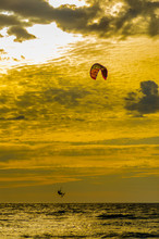 A Kitesurfer In Silhouette Goes Airborne Over Lake Michigan At Grand Haven, Michigan