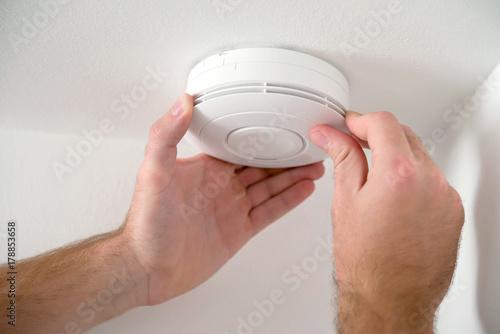 Valokuva Man installing smoke detector